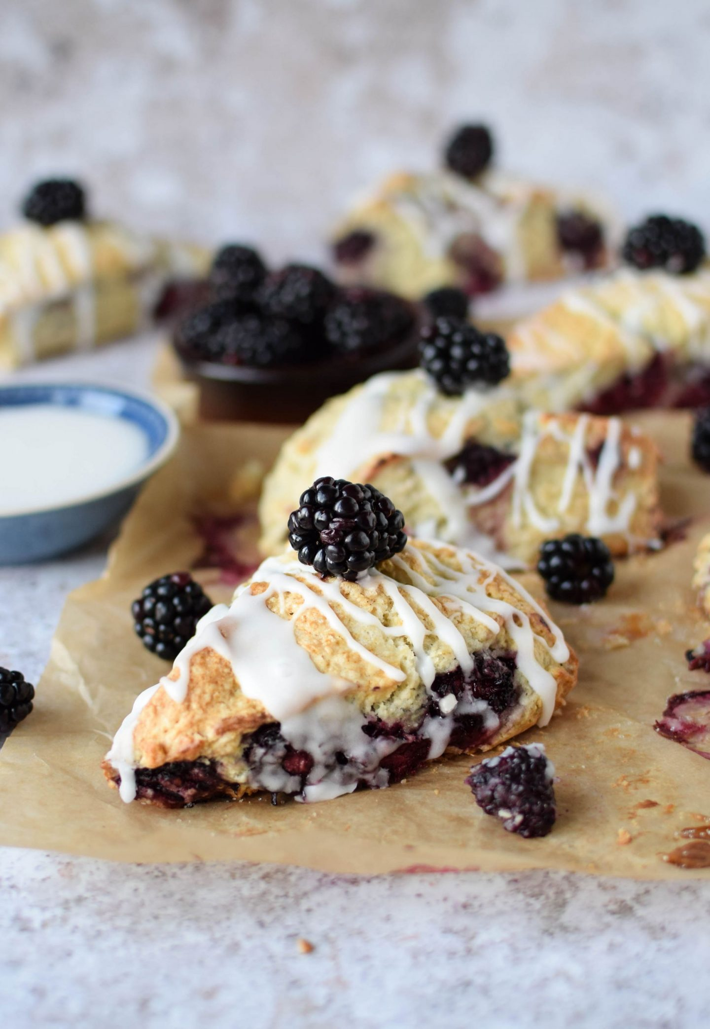 Blackberry and Vanilla Scones on a baking tray drizzled with glaze
