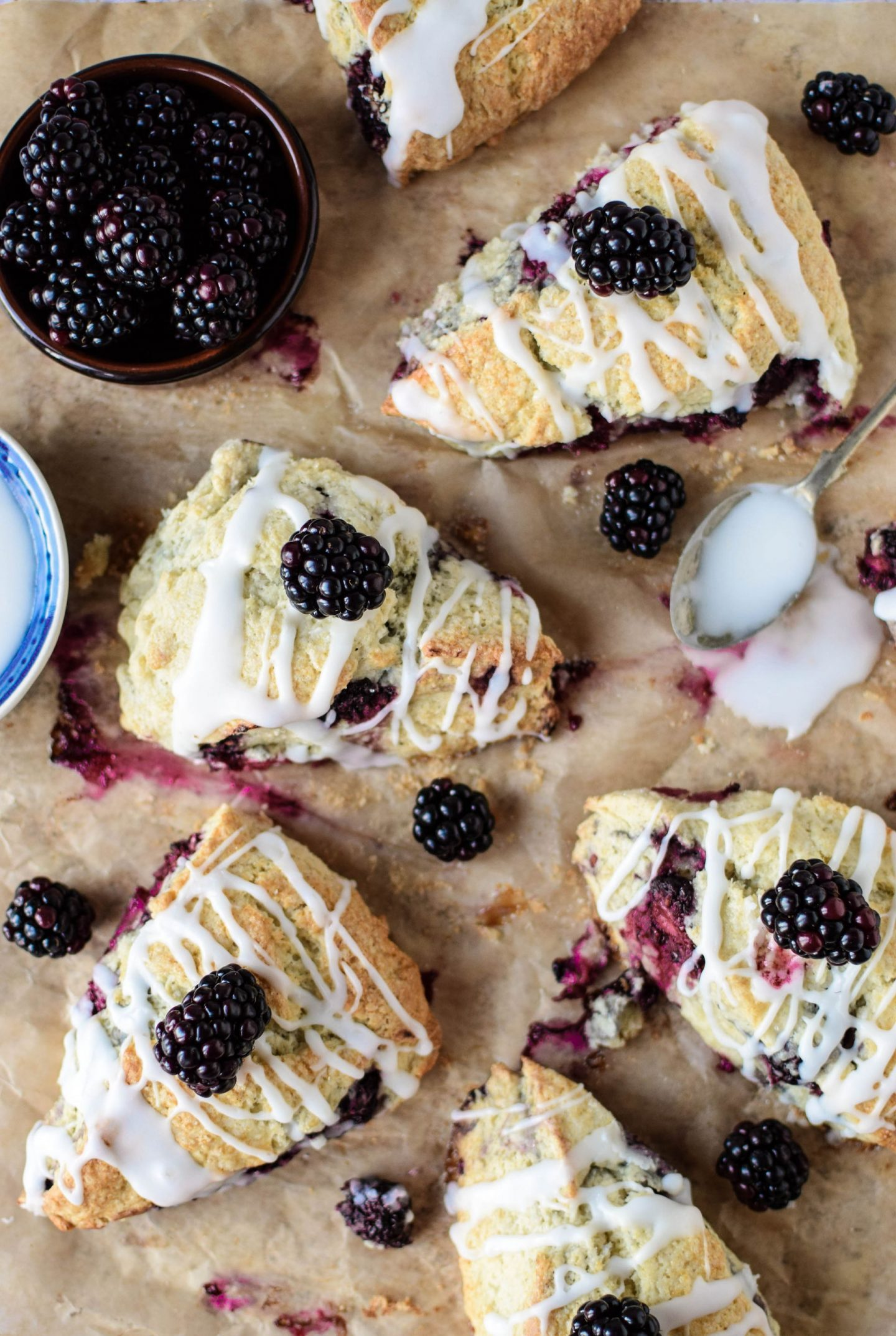Blackberry and Vanilla Scones on a baking tray drizzled with glaze, a spoon sits off to the right