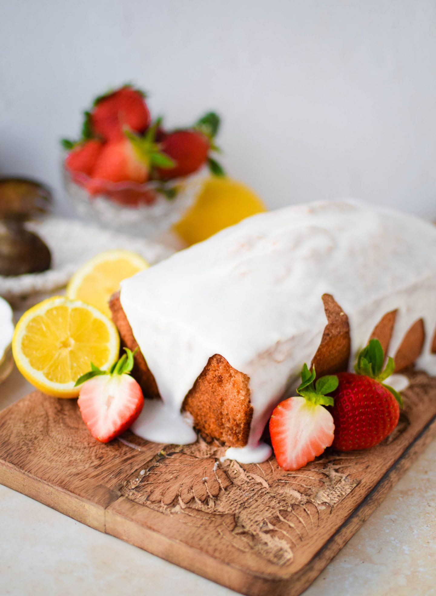 Lemon drizzle cake on a decorative board with some strawberries.