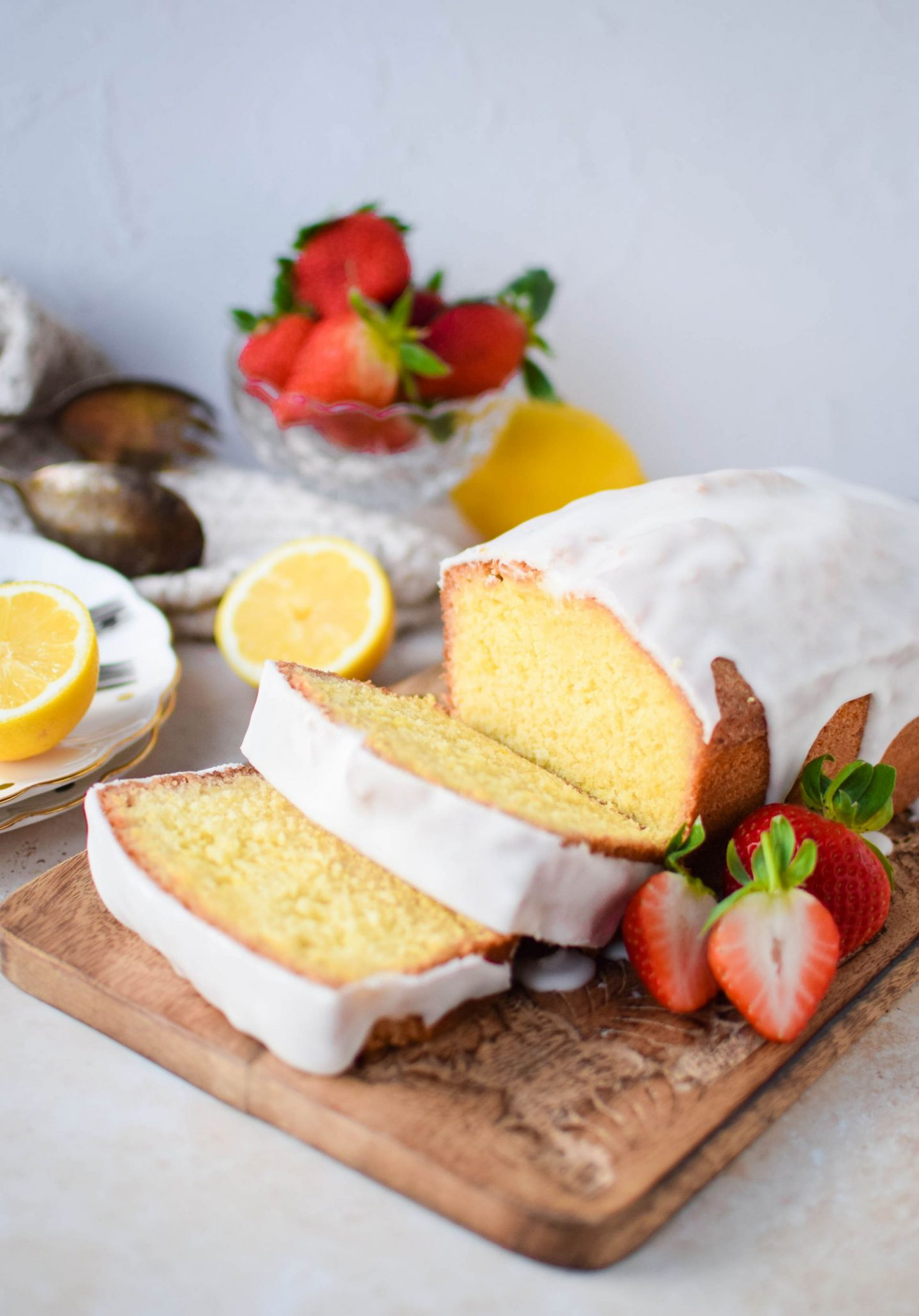 Slices of lemon drizzle cake on a decorative board.
