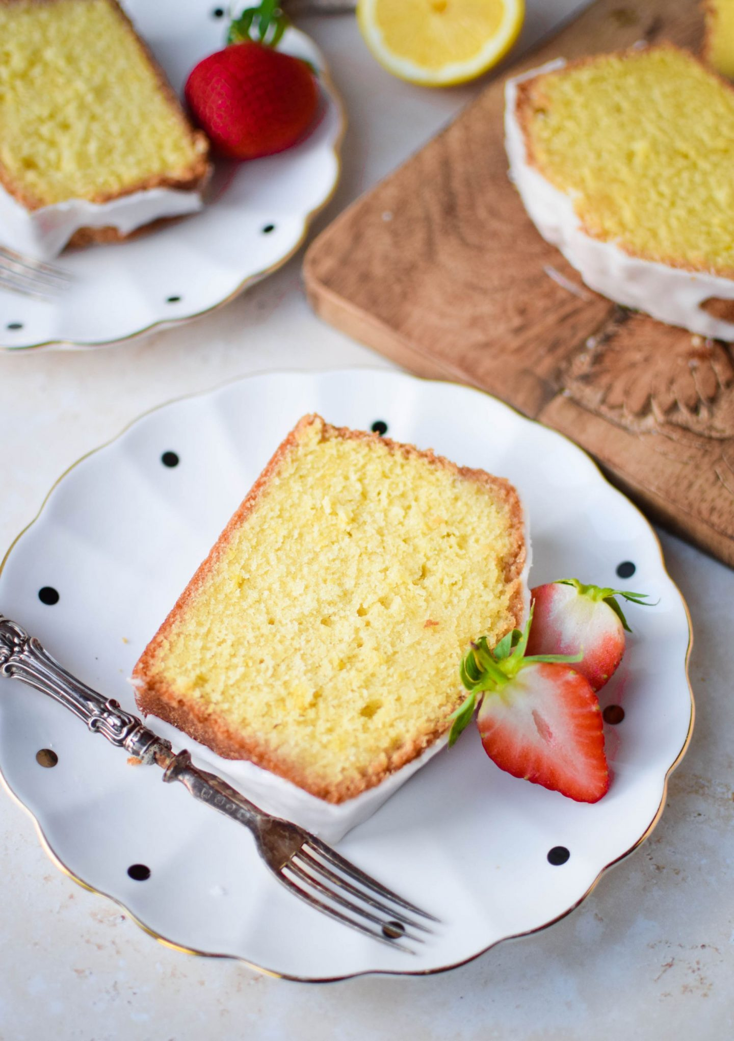 A slice of lemon drizzle cake on a polka dot plate with a halved strawberry.