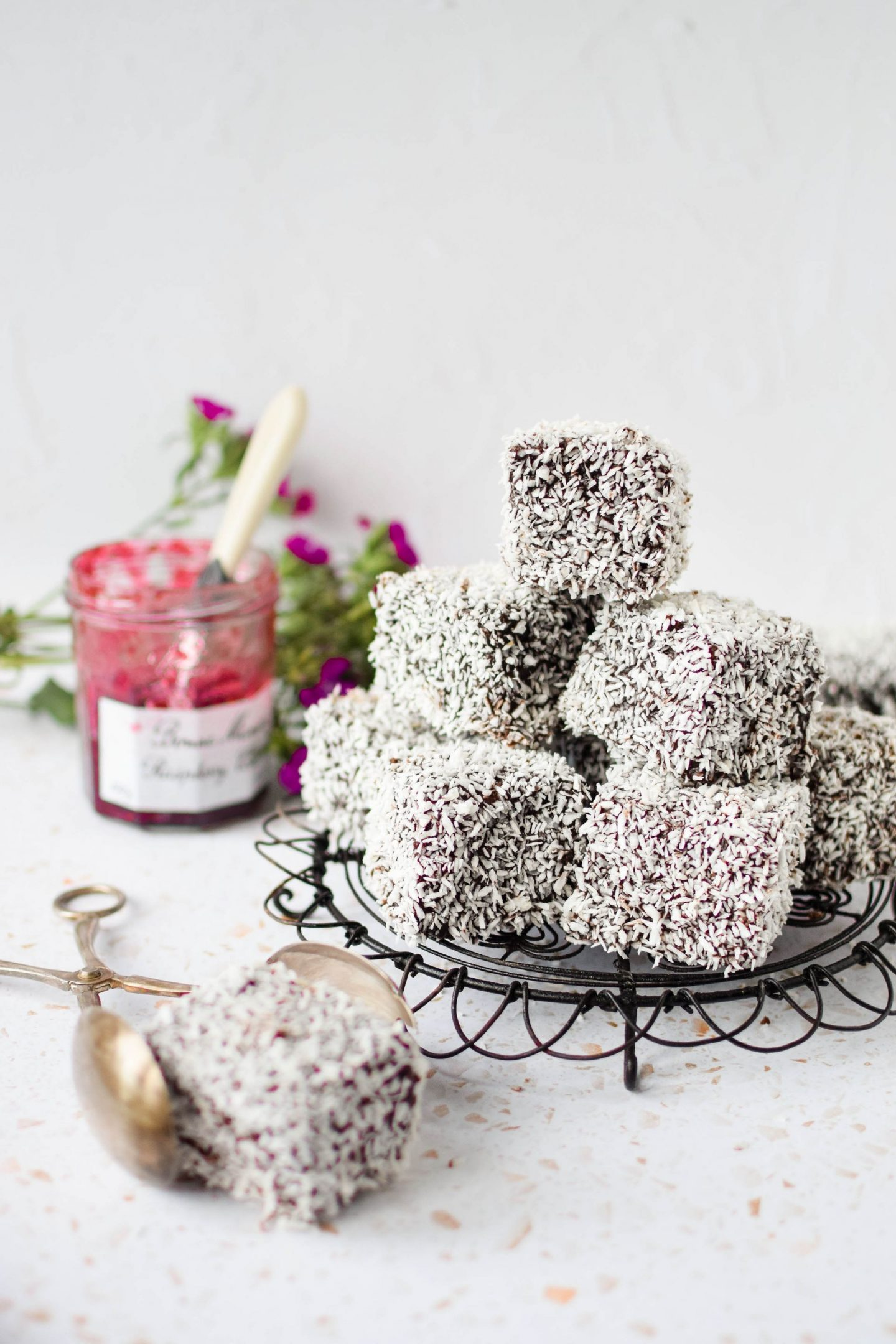 Homemade Lamingtons piled up on a wire cake plate